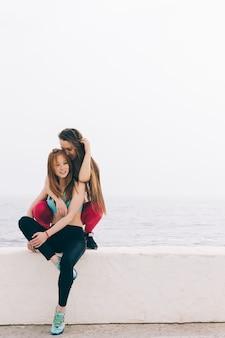 Zwei junge schöne freundinnen, die auf dem hintergrund des meeres sitzen