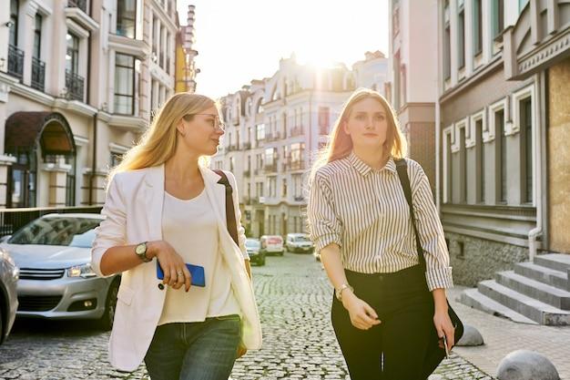 Zwei junge schöne, glückliche studentinnen, die die stadtstraße entlang gehen, frauen lächeln und lachen nach vorne