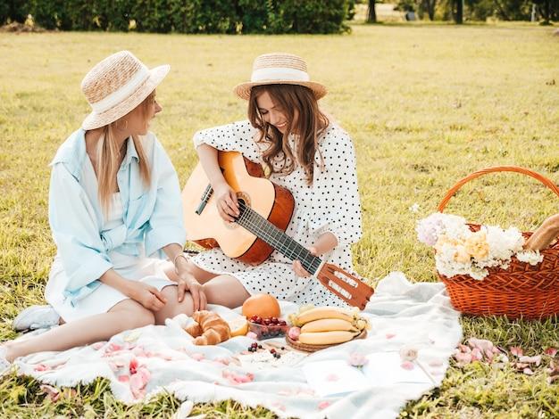 Zwei junge schöne hippie-frau in trendigem sommerkleid und hüten. unbeschwerte frauen, die draußen picknick machen.