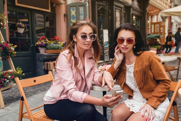 Zwei junge schöne hipsterfrauen, die am café sitzen
