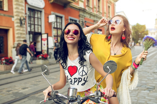 Zwei junge schöne hipsterfrauen, die auf motorradstadtstraße reiten