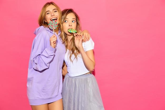 Zwei junge schöne lächelnde blonde hippie-frauen in der modischen sommerkleidung. sorglose heiße frauen, die nahe rosa wand aufwerfen. positive lustige modelle mit lutscher