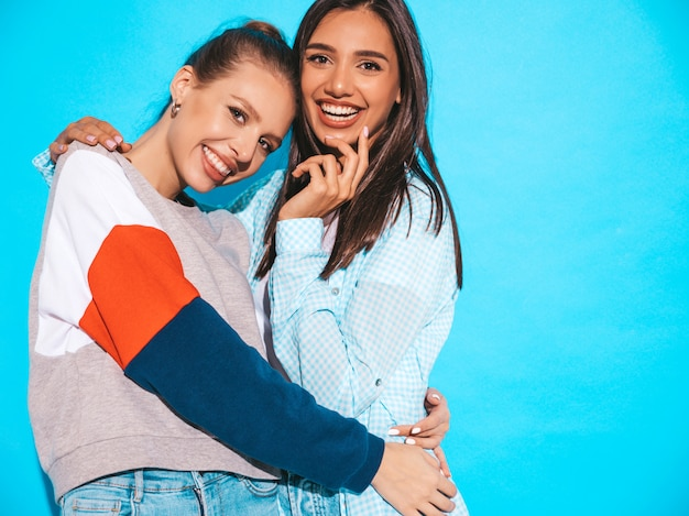 Zwei junge schöne lächelnde blonde hippie-mädchen im bunten t-shirt des modischen sommers kleidet. sexy sorglose frauen, die nahe blauer wand aufwerfen. positive models, die spaß haben
