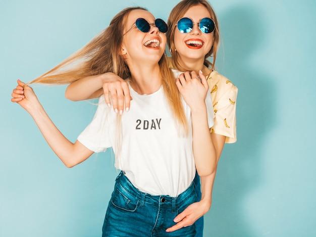 Zwei junge schöne lächelnde blonde hippie-mädchen im bunten t-shirt des modischen sommers kleidet.