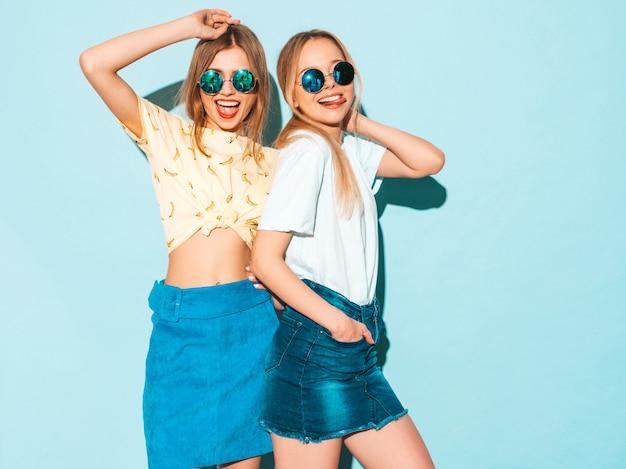 Zwei junge schöne lächelnde blonde hippie-mädchen in den modischen sommerjeans umsäumen kleidung. und zeigt friedenszeichen
