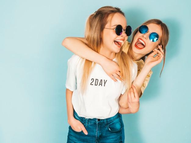 Zwei junge schöne lächelnde blonde hippie-mädchen in den modischen sommerjeans umsäumen kleidung.
