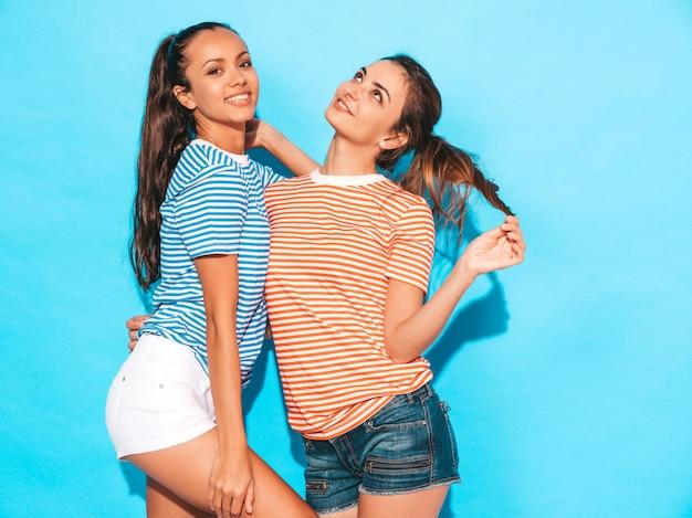 Zwei junge schöne lächelnde brunettehippie-mädchen im bunten hemd des modischen ähnlichen gestreiften sommers kleidet sexy sorglose frauen, die nahe blauer wand im studio aufwerfen positive modelle, die spaß haben