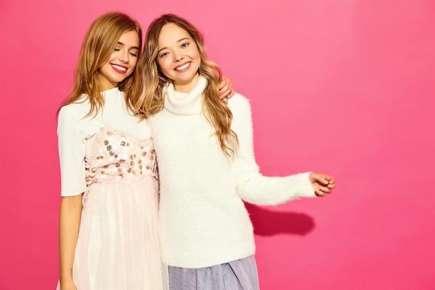Zwei junge schöne lächelnde frauen in den trendigen weißen sommerkleidern
