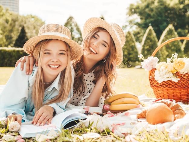 Zwei junge schöne lächelnde frauen in trendigem sommerkleid und hüten. sorglose frauen, die draußen picknick machen.