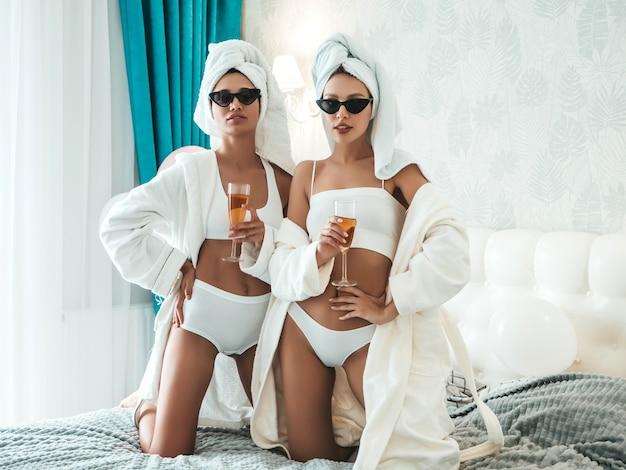 Zwei junge schöne lächelnde frauen in weißen bademänteln und handtüchern auf dem kopf