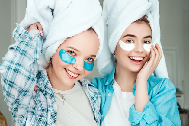 Zwei junge schöne lächelnde frauen mit flecken unter den augen