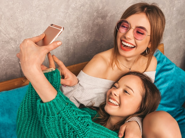 Zwei junge schöne lächelnde herrliche mädchen in der modischen sommerkleidung. sexy sorglose frauen, die im innenraum aufwerfen und selfie nehmen. positive modelle, die spaß mit smartphone haben.