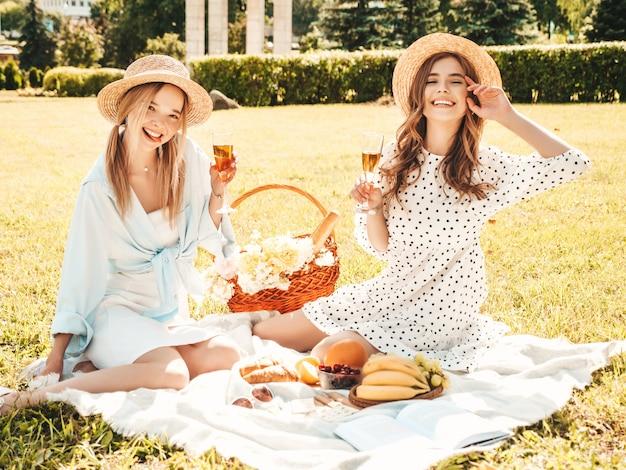 Zwei junge schöne lächelnde hippie-frau im sommerkleid und in den hüten. sorglose frauen, die draußen picknick machen.