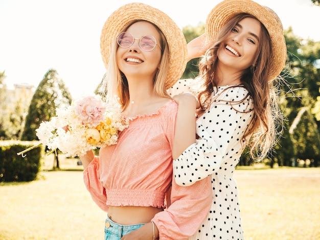 Zwei junge schöne lächelnde hippie-frau im trendigen sommerkleid. sexy sorglose frauen, die im park mit hüten posieren.