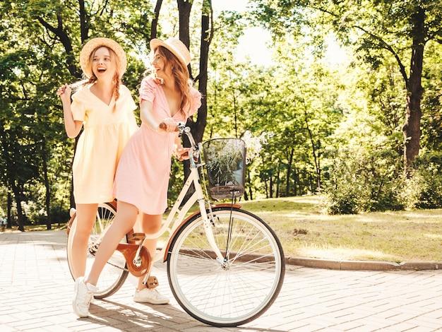 Zwei junge schöne lächelnde hippie-frau im trendigen sommerkleid