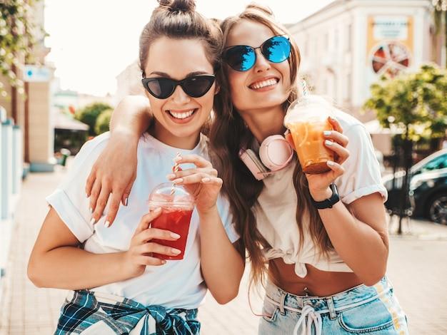 Zwei junge schöne lächelnde hippie-frau in trendiger sommerkleidung