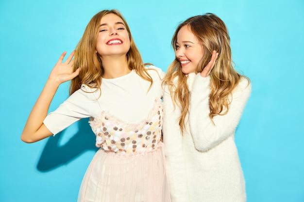 Zwei junge schöne lächelnde hippie-frauen in der weißkleidung des modischen sommers. sexy sorglose frauen, die nahe blauer wand aufwerfen. positive vorbilder