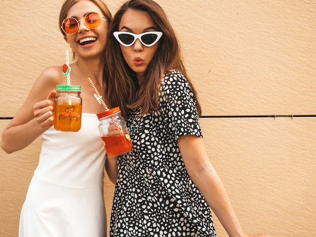Zwei junge schöne lächelnde hippie-mädchen in den modischen sommerkleidern.