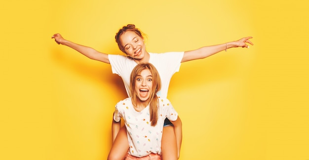 Zwei junge schöne lächelnde hippie-mädchen in der modischen sommerkleidung. sexy sorglose frauen, die nahe gelber wand aufwerfen modell, das auf dem rücken ihrer freundin sitzt und hände anhebt