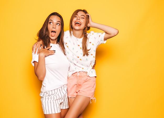 Zwei junge schöne lächelnde hippie-mädchen in der modischen sommerkleidung. sexy sorglose frauen, die nahe gelber wand aufwerfen. positive models werden verrückt und haben spaß