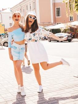 Zwei junge schöne lächelnde hippie-mädchen in der modischen sommerkleidung und im panama-hut.
