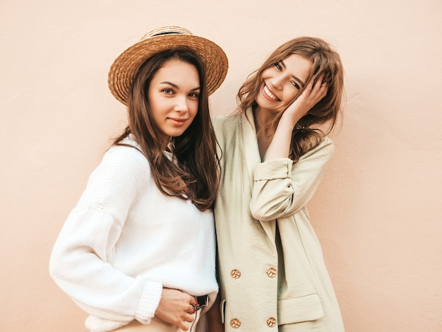 Zwei junge schöne lächelnde hipster-frau im trendigen weißen pullover und mantel