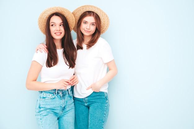 Zwei junge schöne lächelnde hipster-frau in trendigem weißem t-shirt und jeanskleidung