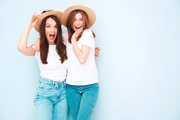 Zwei junge schöne lächelnde hipster-frauen in trendigen weißen t-shirts und jeanskleidern im gleichen sommer