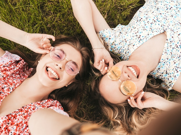 Zwei junge schöne lächelnde hipster-mädchen im trendigen sommer-sommerkleid. sexy sorglose frauen, die auf dem grünen gras in der sonnenbrille liegen. positive modelle, die spaß haben. draufsicht. aufnehmen von selfie-fotos auf smartphone