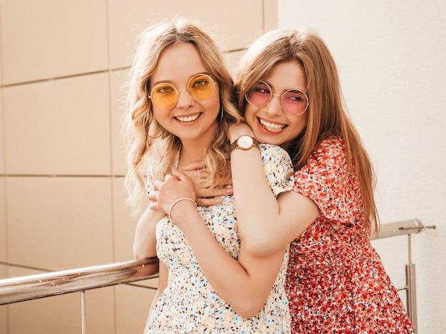 Zwei junge schöne lächelnde hipster-mädchen im trendigen sommer-sommerkleid. sexy sorglose frauen, die auf dem straßenhintergrund in den hüten aufwerfen. positive models, die spaß haben und sich umarmen. sie werden verrückt