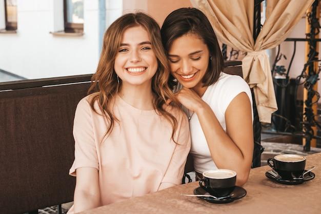 Zwei junge schöne lächelnde hipster-mädchen im trendigen sommer-sommerkleid. sorglose frauen, die im veranda-café plaudern und kaffee trinken. positive modelle, die spaß haben und kommunizieren