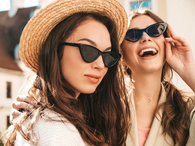 Zwei junge schöne lächelnde hipster-mädchen im trendigen weißen pullover und mantel