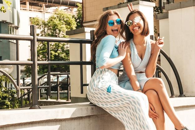 Zwei junge schöne lächelnde hipster-mädchen in der trendigen sommerkleidung. sexy sorglose frauen, die auf dem straßenhintergrund in der sonnenbrille aufwerfen. positive models, die spaß haben und verrückt werden