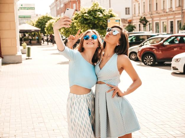 Zwei junge schöne lächelnde hipster-mädchen in der trendigen sommerkleidung. sexy sorglose frauen, die auf dem straßenhintergrund in der sonnenbrille aufwerfen. sie machen selfie-selbstporträtfotos auf dem smartphone bei sonnenuntergang