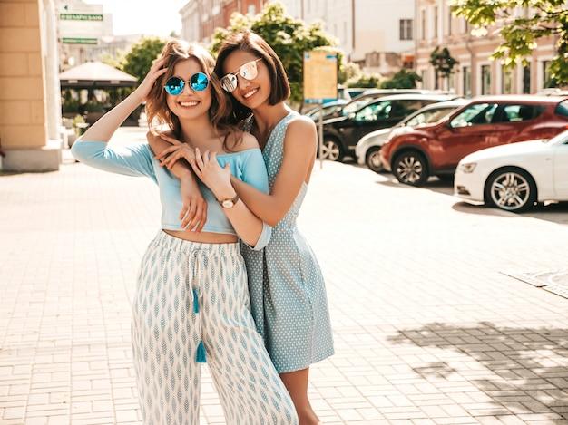 Zwei junge schöne lächelnde hipster-mädchen in der trendigen sommerkleidung. sexy sorglose frauen, die auf straßenhintergrund in der sonnenbrille aufwerfen. positive models, die spaß haben und sich umarmen