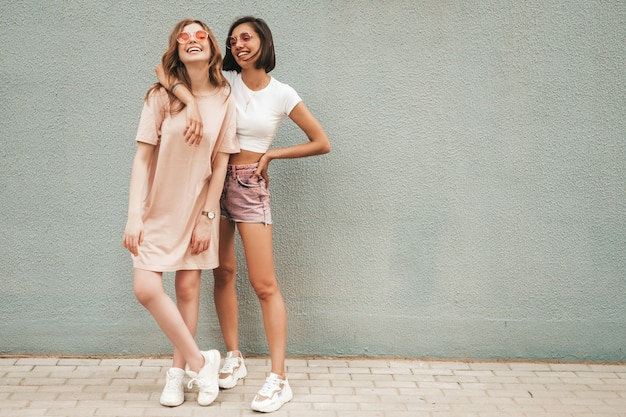 Zwei junge schöne lächelnde hipster-mädchen in der trendigen sommerkleidung. sexy sorglose frauen, die nahe wand in der straße in der sonnenbrille aufwerfen. positive models, die spaß haben und sich umarmen