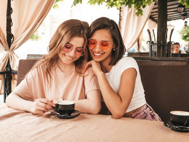 Zwei junge schöne lächelnde hipster-mädchen in trendigen sommer-freizeitkleidung. sorglose frauen, die im veranda-terrassencafé plaudern und kaffee trinken. positive modelle, die spaß haben und kommunizieren
