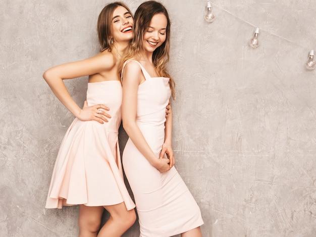 Zwei junge schöne lächelnde mädchen in den hellrosa kleidern des modischen sommers. sexy sorglose frauenaufstellung. positive models, die spaß haben