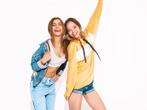 Zwei junge schöne lächelnde mädchen in den modischen sommerjeans kleidet. sexy sorglose frauen. positive vorbilder