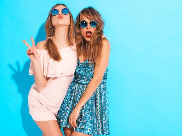 Zwei junge schöne lächelnde mädchen in den modischen sommerkleidern und -sonnenbrille. sexy sorglose frauenaufstellung. positive vorbilder
