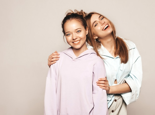 Zwei junge schöne lächelnde mädchen in der modischen sommerkleidung. sexy sorglose frauen. positive vorbilder