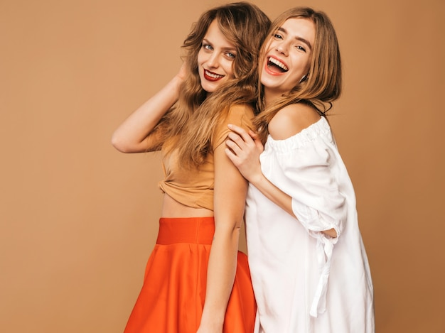 Zwei junge schöne lächelnde mädchen in der modischen sommerkleidung. sexy sorglose frauenaufstellung. positive vorbilder