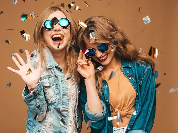 Zwei junge schöne lächelnde mädchen in der modischen sommerkleidung und -sonnenbrille. sexy sorglose frauenaufstellung. positive schreiende modelle unter konfetti