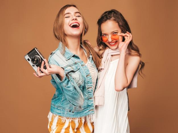Zwei junge schöne lächelnde mädchen in der zufälligen kleidung und in der sonnenbrille des modischen sommers. sexy sorglose frauenaufstellung. fotografieren mit der retro-kamera