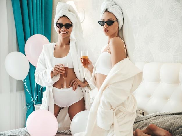 Zwei junge schöne lächelnde mädchen in weißen bademänteln und handtüchern auf dem kopf