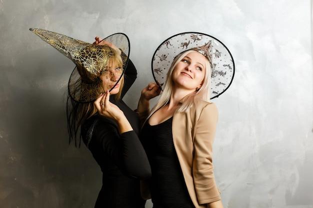 Zwei junge schöne mädchen, die das schwarze kleid der hexe bildet party tragen