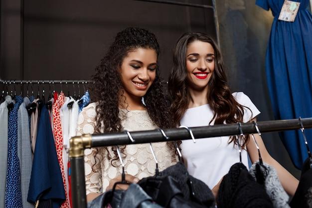 Zwei junge schöne mädchen, die im einkaufszentrum einkaufen.