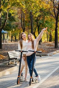 Zwei junge schöne mädchen fahren an einem warmen herbsttag mit elektrorollern im park.