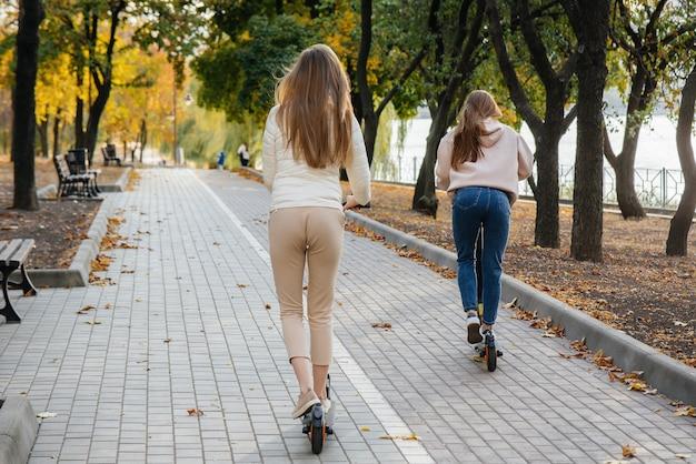 Zwei junge schöne mädchen in masken fahren an einem warmen herbsttag mit elektrorollern im park. im park spazieren gehen.