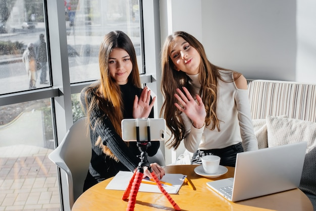 Zwei junge schöne mädchen sitzen in einem café, nehmen videoblogs auf und kommunizieren in sozialen netzwerken.